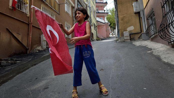Een meisje speelt met de Turkse vlag in de buurt waar president Recep Tayyip Erdogan geboren is.