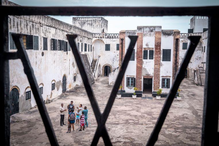 Een groep toeristen tijdens een rondleiding op de binnenplaats van fort Elmina. In het hekwerk van het balkon is o.a. de letter W verwerkt, van West Indische Compagnie, de handelsmaatschappij die het Nederlandse monopolie op de trans-atlantische slavenhandel had. Beeld Sven Torfinn