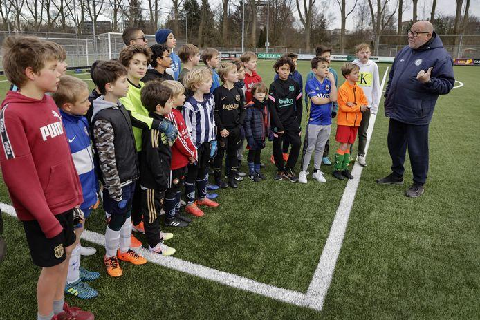 Voorzitter Michel Boerman instrueert de voetballertjes op het complex van Neptunus-Schiebroek.