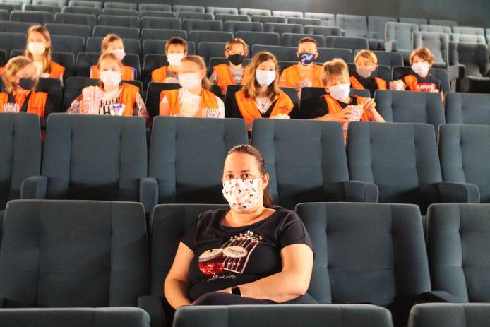 Véronique Meyfroodt van Cinema Varietes met op de achtergrond enkele leerlingen van basisschool Klim Op.