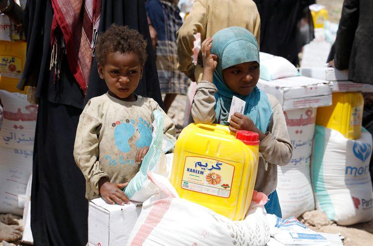 Ontheemde Jemenitische kinderen aan een voedselbedeling in de buitenwijken van hoofdstad Sanaa.  Beeld EPA