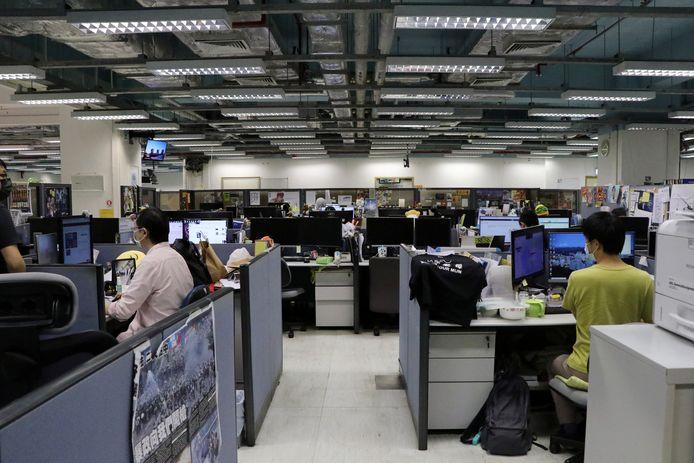 Journalisten en medewerkers aan de slag op de redactie van de pro-democratische krant Apple Daily, een dag nadat de politie er binnenviel en vijf directeurs gearresteerd werden.