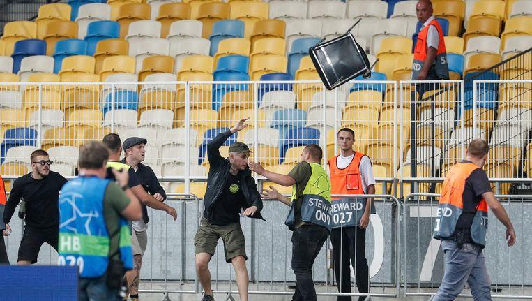 Een hooligan van Dinamo Kiev gooit een stoel naar een Ajax-fan. Hier grepen de stewards wel in. Beeld epa