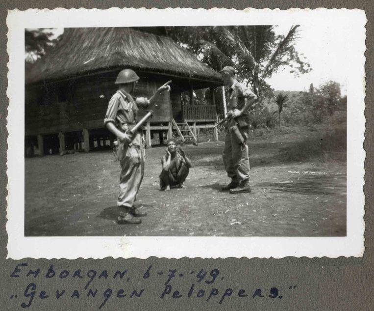 Tijdens een doorzoekingsactie van een kampong, vermoedelijk op Sumatra, ondervragen Nederlandse militairen op 6 juli 1949 een Indonesische gevangene. Het onderschrift verwijst naar 'peloppers' (ook wel 'ploppers'), dit was de denigrerende term die zij vaak voor vijandelijke strijders gebruikten.  Beeld Foto uit een album, eigenaar onbekend © Collectie Nederlands Instituut voor Militaire Historie