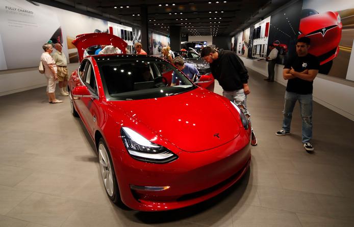 Potentiële kopers bewonderen een Tesla Model 3 in een showroom in Denver. Uit Amerikaans onderzoek blijkt dat de veiligheidssystemen van deze moderne auto regelmatig falen.