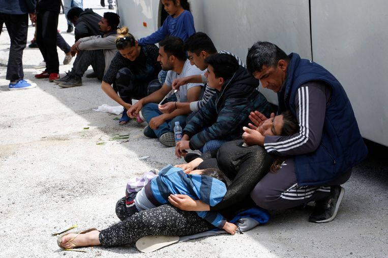 Een vrouw valt flauw als asielzoekers urenlang wachten om naar de Bosnische stad Mostar te worden gebracht voor opvang. Beeld AP