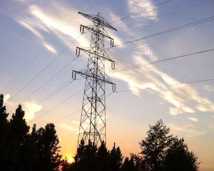 Schone energieleverancier 'de zon' zakt weg achter een 150-kV-hoogspanningsmast bij Zetten, op de lijn Dodewaard-Nijmegen.