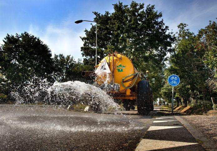Milheezerweg in Deurne wordt nat gemaakt om ervoor te zorgen dat asfalt niet beschadigt.