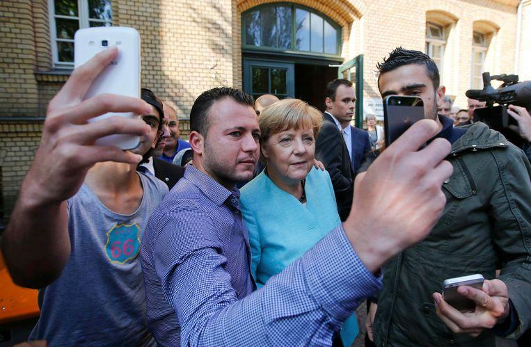 Duits bondskanselier Angela Merkel gaat op de foto met Syrische vluchtelingen in Berlijn. Beeld REUTERS