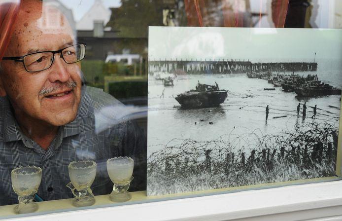 Carlos Eckardt achter de voorruit van zijn huis met een foto van de landing van de bevrijders.