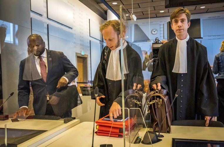 Advocaat Jelle Klaas (M) samen met Mpanzu Bamenga (L) voorafgaand aan de uitspraak van de rechtbank of de Koninklijke Marechaussee zich schuldig maakt aan etnisch profileren bij het controleren van mensen die het land binnenkomen.  Beeld ANP