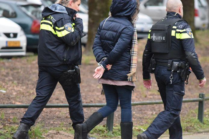 Een aangehouden verdachte wordt geboeid afgevoerd na de schietpartij in een flat in de Nijmeegse wijk Lankforst.
