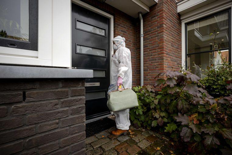 Een huisarts in beschermende kleding arriveert bij een patiënt thuis. Ook de huisartsen krijgen nu voorrang in de vaccinatierij. Beeld ANP