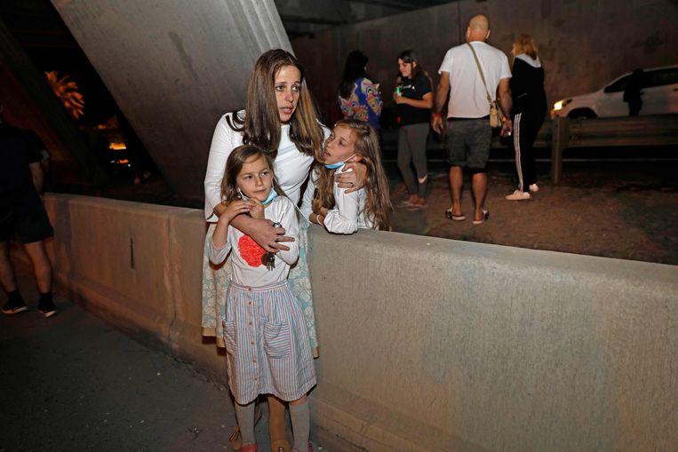 Mensen zoeken dekking onder een brug in Tel Aviv, nadat raketten op Israël werden gelanceerd vanuit de Gazastrook. Beeld AFP