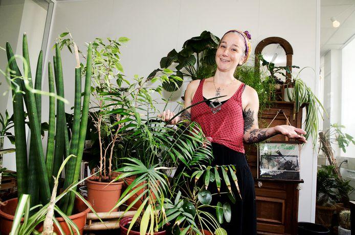 Plantenverzorger Fem van der Rijst tussen een aantal van door haar opgeknapte kamerplanten.