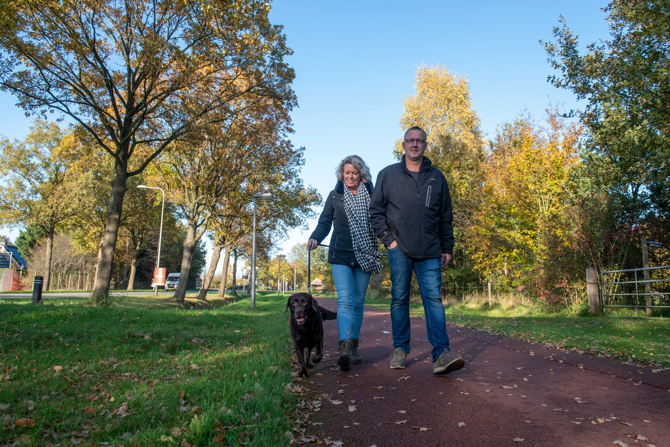 Hondenbezitters die langs de Koesteeg in Dalfsen wandelen. De viervoeter is aangelijnd, zoals het hoort.