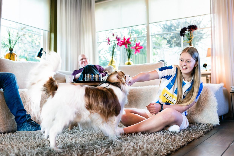 Fleur Harshagen (18) thuis bij haar vader (links buiten beeld) in Lienden, met haar opa op de bank. Al vijftien jaar verplaatst Fleur zich tweemaal per week tussen de huizen van haar co-ouderende vader en moeder.  Beeld Katja Poelwijk