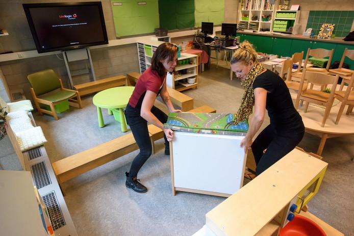 Malon Arends en Marloes Lieftink sjouwen met een boekenkast.