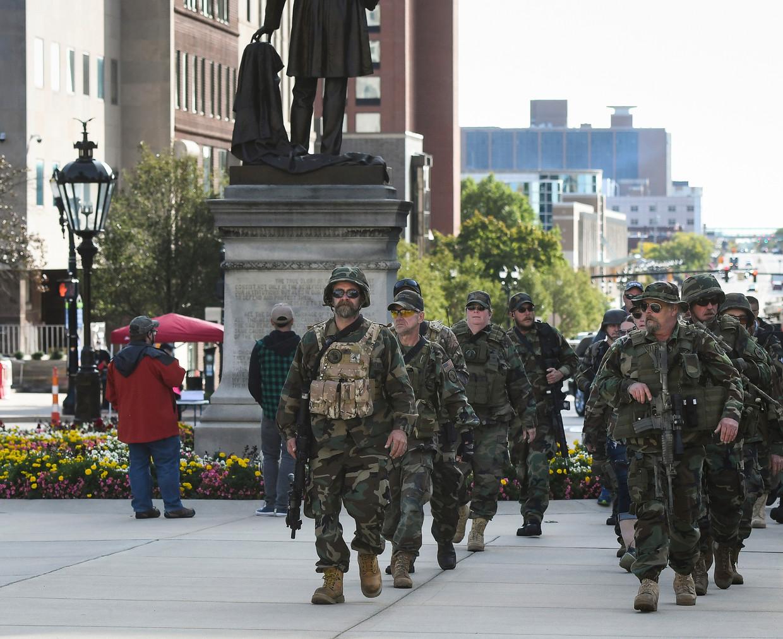 Leden van de Michigan Home Guard militie marcheren naar het parlementsgebouw van hun staat Michigan hun steun te betuigen aan het recht op wapenbezit.  Ze protesteerden ook tegen maatregelen om corona in te dammen.  Beeld AP