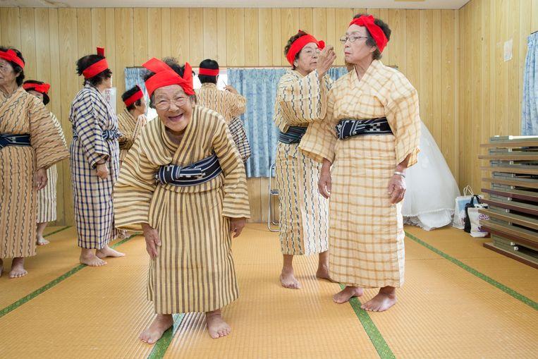 De leden van vrouwenkoor 'KBG84' voor 80-plussers van Okinawa, Japan, maken zich klaar voor een optreden. Beeld Lieve Blancquaert