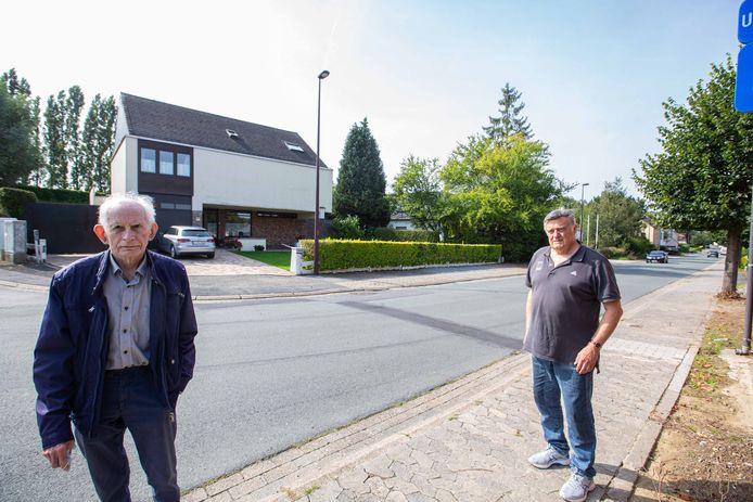 """Johan Van Damme (links) met Werner Thibaut voor de woning van die laatste. De gevel vertoont langs de buitenzijde enkele scheuren. """"Een gevolg van de slechte staat van het wegdek hier"""", klink het."""