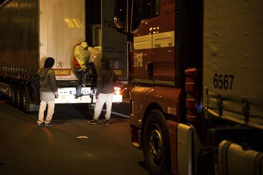 Migranten klimmen in een vrachtwagen in Calais.