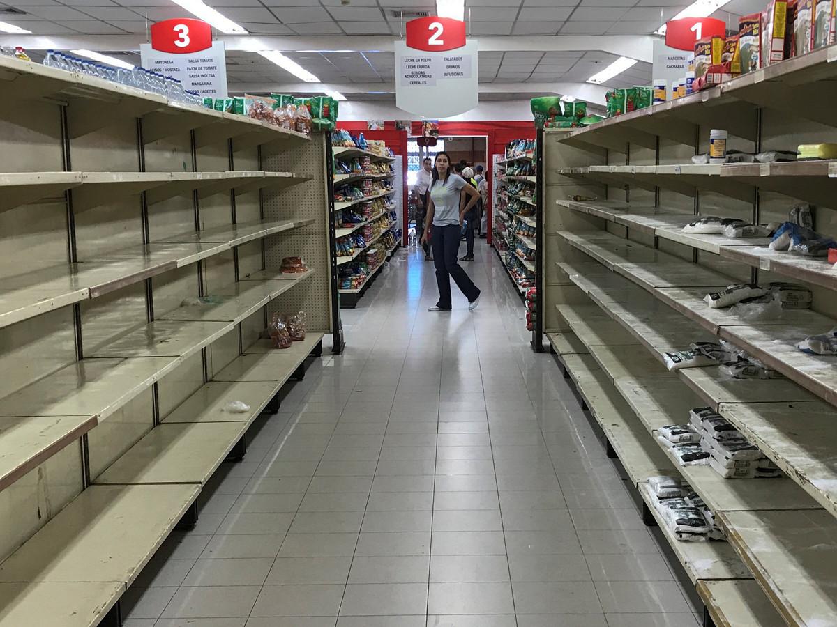 Een vrouw wandelt voorbij lege winkelrekken in Caracas.