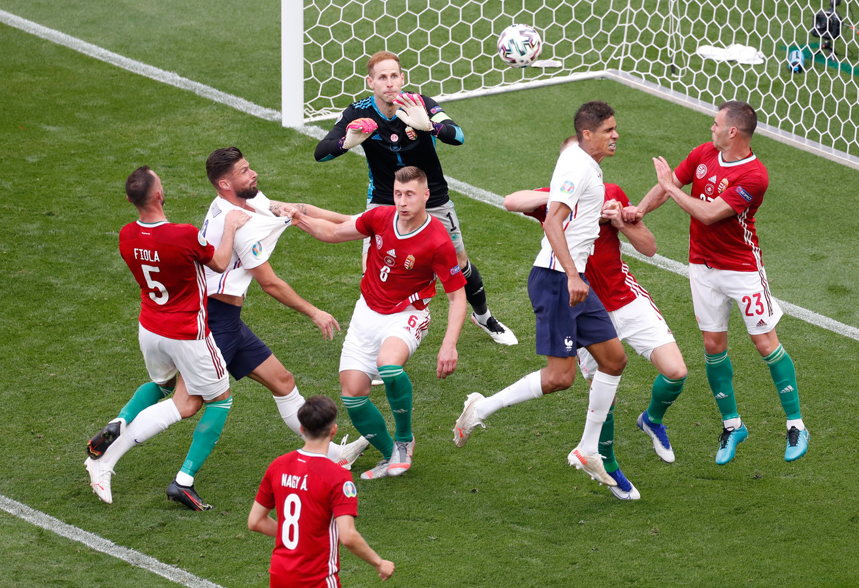 Olivier Giroud wordt door twee Hongaren vastgehouden, maar krijgt geen strafschop.