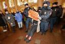 Een betoger met een bord 'Vrijheid voor Navalny' wordt afgevoerd door agenten.