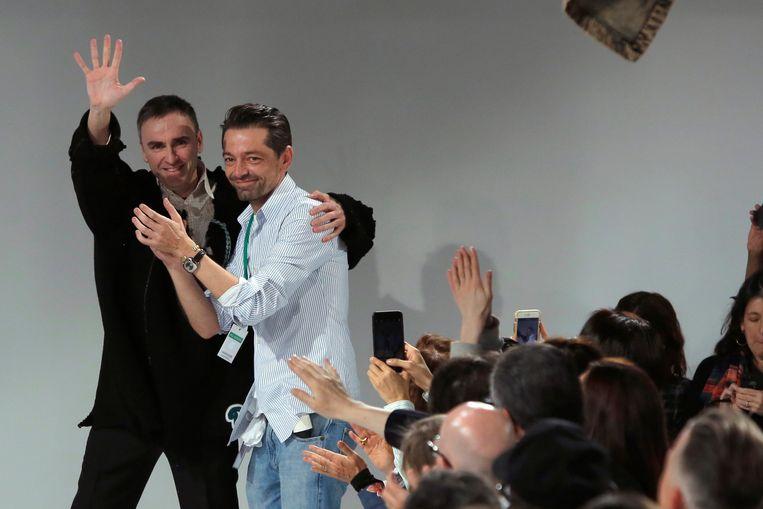 Raf Simons (links) en zijn rechterhand Pieter Mulier nemen het applaus in ontvangst na afloop van de show. Beeld REUTERS