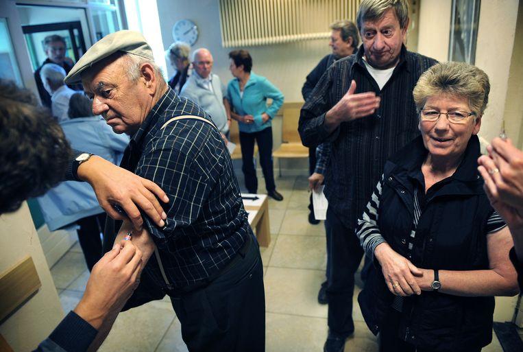 Ouderen halen hun jaarlijkse griepprik bij de huisarts, Maasbommel, 2009. Beeld Marcel van den Bergh / de Volkskrant