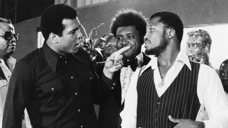 Muhammad Ali met een vermanende vinger naar Joe Frazier, bokspromotor Don King kijkt toe. Beeld AP