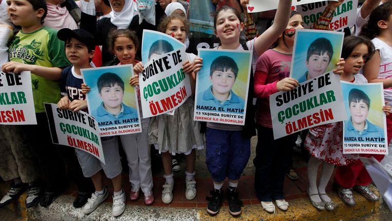 Demonstratie voor de Syrische ambassade in Istanboel. Kinderen dragen het portret van de 13-jarige Hamza al-Khatib die werd gemarteld en vermoord. Beeld REUTERS
