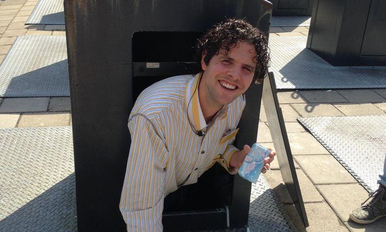 Behulpzame supermarktmedewerker duikt in container voor smartphone