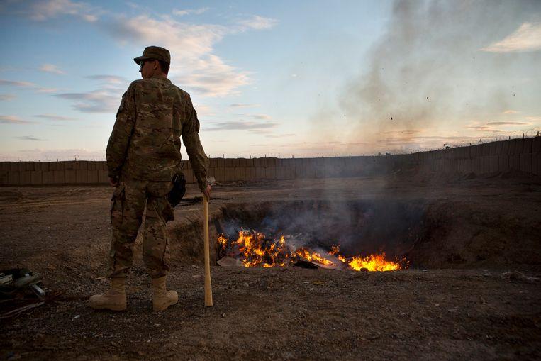 Een Amerikaanse militair bij een verbrandingskuil in de Afghaanse provincie Kandahar.  Beeld Reuters