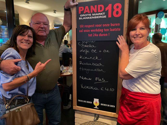 Eigenaar Michel Van den Brande met zijn partner Sofie (l) en uitbaatster Linda bij het nieuwe bord dat de nieuwe maatregel aankondigt.