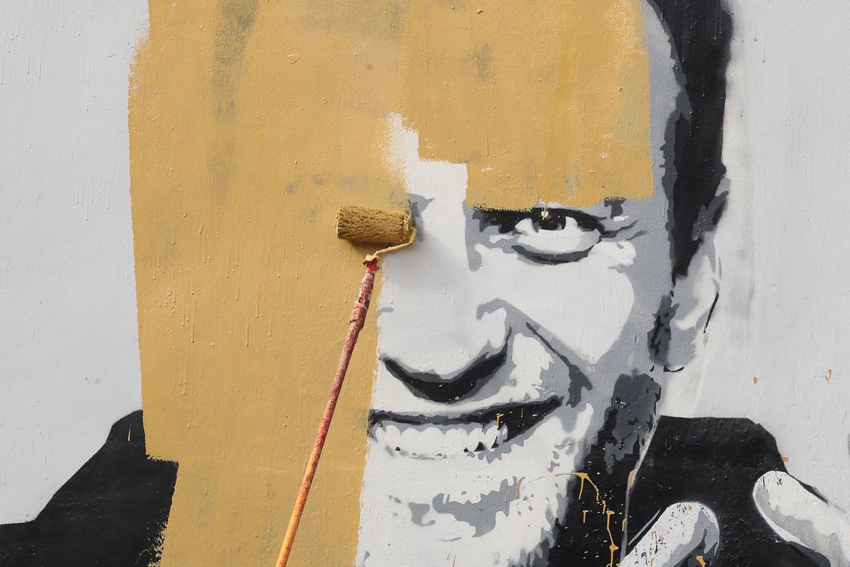 Een muurschildering die Navalny afbeeldt wordt overschilderd Beeld Alexander Demianchuk/TASS