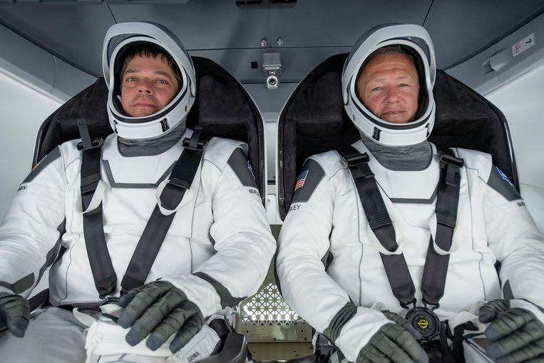 De astronauten Bob Behnken (L) en Doug Hurley aan boord van de Dragon-capsule. Beeld EPA