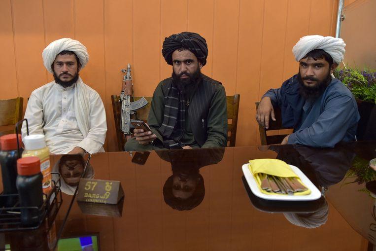 Strijders van de Taliban in een restaurant in Kaboel.  Beeld AFP