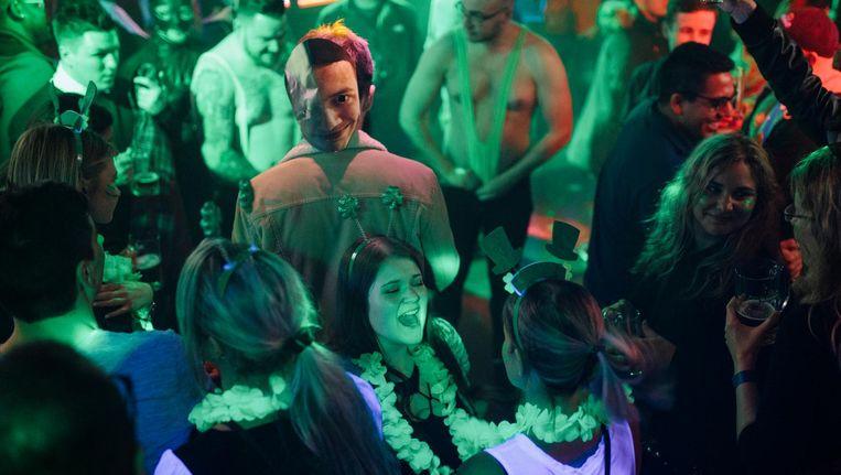 Toeristen die meedoe aan een pub crawl in de Red Light Bar aan de Oudezijds Achterburgwal. Beeld Marc Driessen