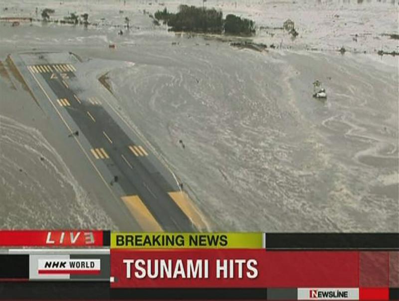 Tsunamigolven overspoelen de startbaan op de luchthaven van het Japanse Sendai.