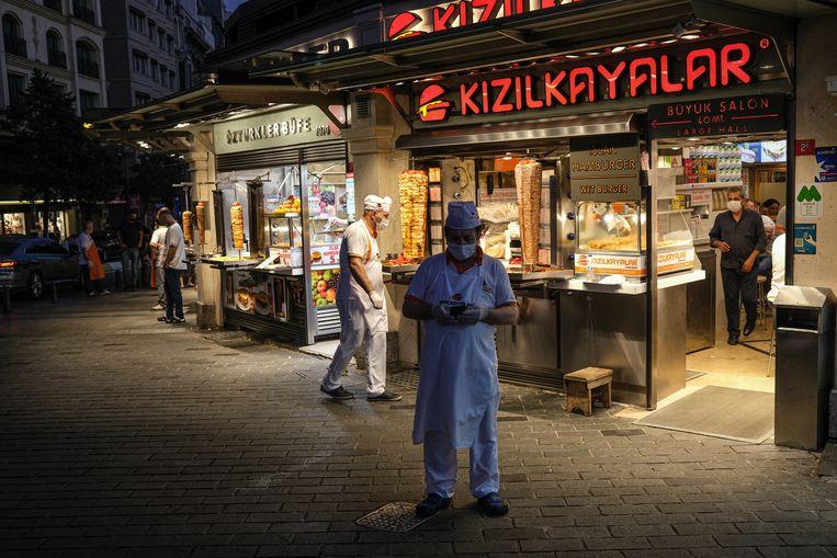 Een horecamedewerker kijkt op zijn telefoon op het Taksimplein, hartje Istanbul. De Turkse president Erdogan is in de loop der jaren steeds gevoeliger geworden voor kritiek op sociale media.  Beeld EPA