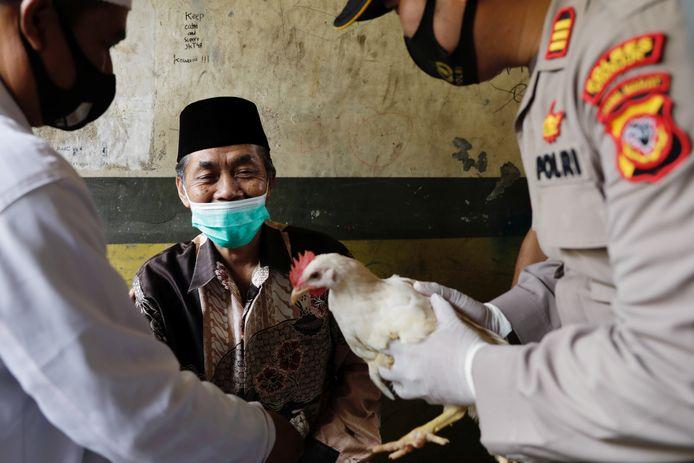 De 72-jarige Lili Dinata uit de stad Sindanglaya in West-Java bij de overhandiging van een levende kip na zijn eerste coronaprik op 15 juni.