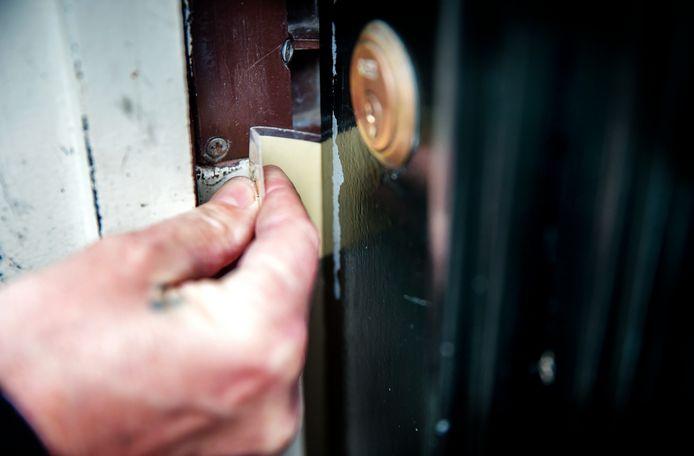 Een inbreker opent met een pasje of een stuk plastic een voordeur, ook wel flipperen genoemd. Foto ter illustratie.