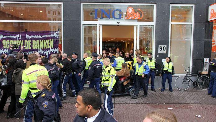 De politie arresteert betogers. Het bankfiliaal was zaterdag open op het moment van de bezetting, waardoor medewerkers en klanten veel hinder ondervonden van de actie, aldus een politiezegsvrouw.