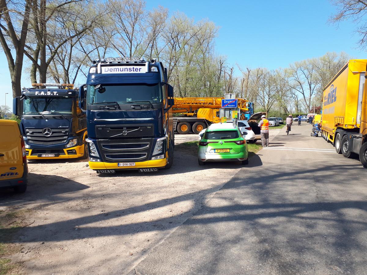 Vrachtwagens en kraanwagens staan klaar in Drunen om de fietsbrug te lichten.