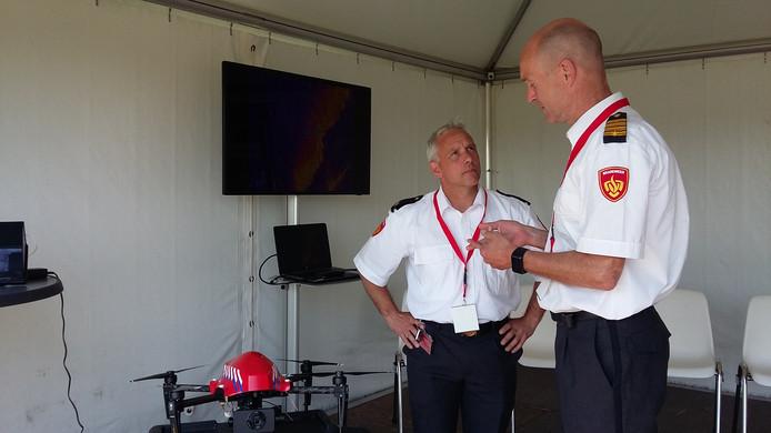 Dronespecialist Martijn Zagwijn van de brandweer Twente geeft op het congres op Papendal een Friese collega tekst en uitleg over de inzet van drones.