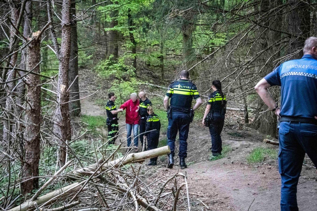 De man is gevonden en wordt door hulpverleners geholpen om weer het bos bij De Steeg uit te komen.
