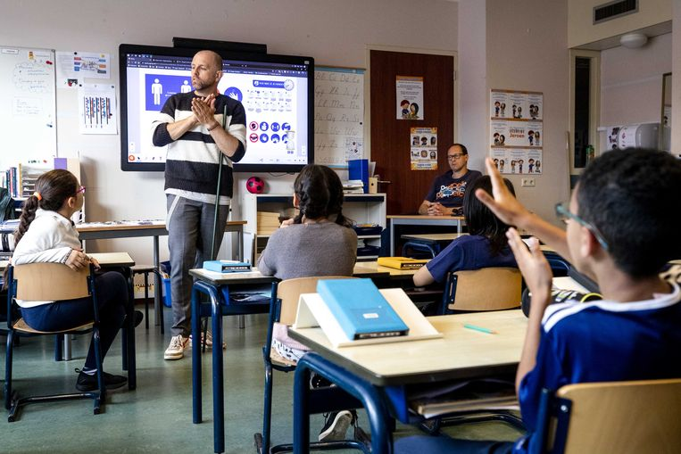 Een leraar laat in de klas zien hoe basisschoolleerlingen hun handen moeten wassen. Beeld ANP