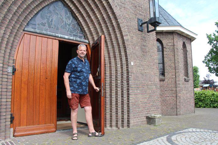 Johnny Lankheet, voorzitter Visiegroep Toekomst H. Caecilia Rietmolen in de deuropening van de kerk, met rechts achter de heg de speelplaats van basisschool St Jozef.